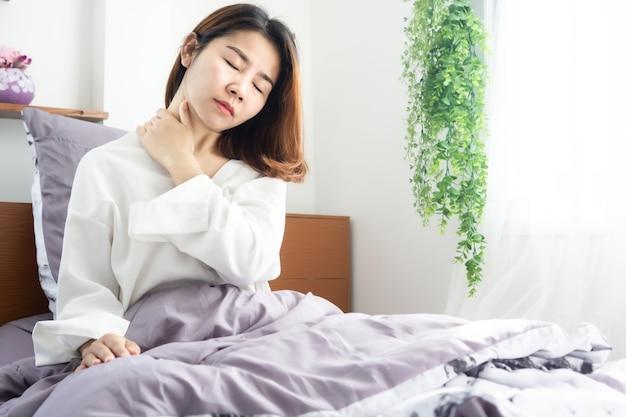 Azjatka z bólem szyi budzi się w łóżku
