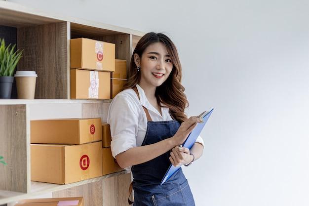 Azjatka z podsumowaniem zamówienia, właścicielką sklepu internetowego, pakuje i wysyła za pośrednictwem prywatnej firmy transportowej. koncepcje sprzedaży i zakupów online.