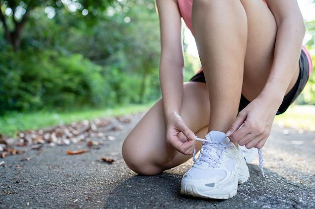 Azjatka zapina paski do butów przed bieganiem