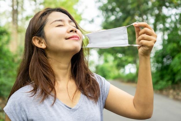 Azjatka zdejmuje maskę i oddycha głęboko świeżym powietrzem natury