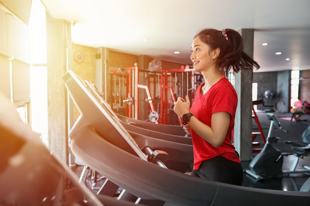 Azjatki biegają sportowe buty na siłowni, podczas gdy młoda kaukaska kobieta biega na bieżni