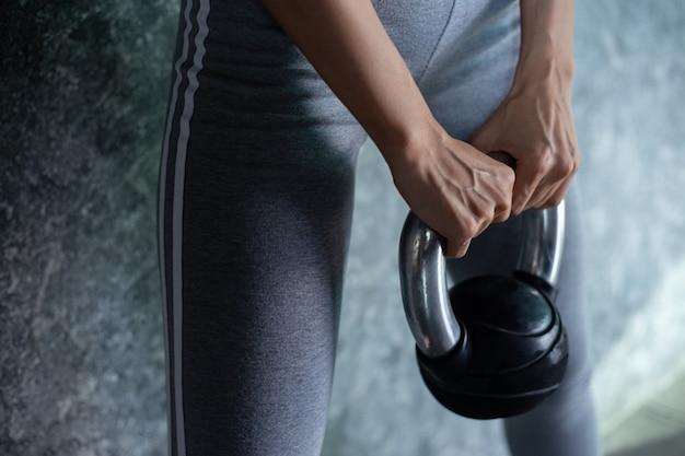 Azjatki ćwiczą z kettlebell na siłowni.