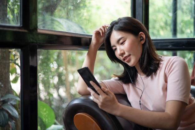 Azjatki pracują i słuchają muzyki na telefonach komórkowych.