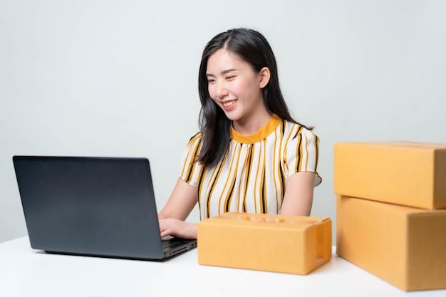 Azjatki rozpoczynają nowy biznes na rynku internetowym. azjatki sprawdzają produkty, przygotowują się do dostarczenia produktów klientom. koncepcja mśp