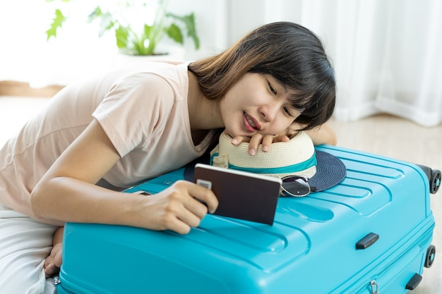 Azjatki siedzą, patrząc na swoje paszporty i uśmiechając się radośnie. kobieta pakująca walizkę, aby przygotować się do podróży na wakacje.
