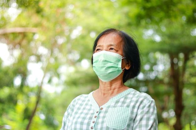 Azjatki starsze kobiety noszące zielone maski stojące w ogrodzie. koncepcja ochrony przed koronawirusem. dystans społeczny. skopiuj miejsce