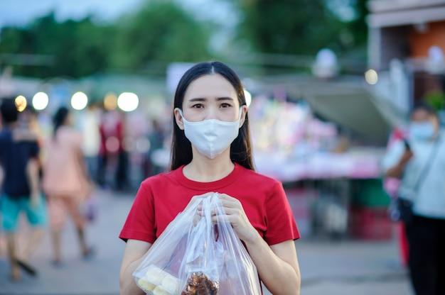 Azjatki tajki używają maski na twarz lub maski chirurgicznej chronią wirusa koronowego, covid 19, nowe normalne życie ludzi w azji południowo-wschodniej, tajki używają maski na ulicy spacerowej