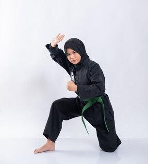 Azjatki w chustach na głowach noszą mundury pencak silat z przysadzistymi zielonymi pasami podczas wykonywania ruchów obronnych