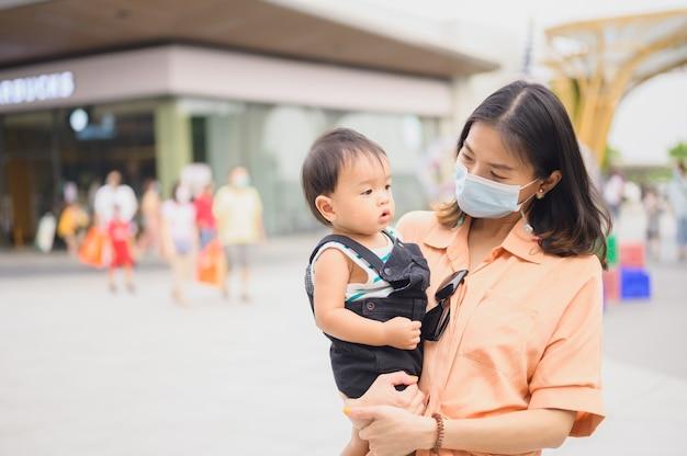 Azjatki w ochronnej sterylnej masce medycznej z synem. zanieczyszczenie powietrza, wirus, koncepcja koronawirusa