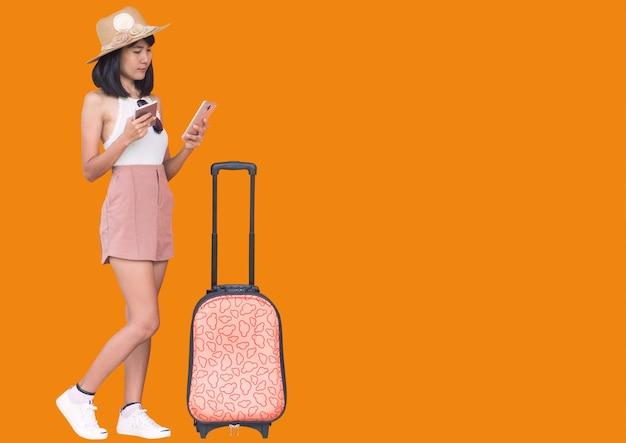 Azjatki w ubraniach podróżniczych z bagażem, które trzyma paszport i telefon komórkowy, aby znaleźć informacje dotyczące podróży lub lotów i atrakcji turystycznych bez utraty na pomarańczowej ścianie. koncepcja lato.