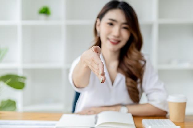 Azjatki wyciągają ręce, jakby prosiły o uścisk dłoni, bizneswoman wyciąga rękę do przodu, by uścisnąć partnera biznesowego, uścisk dłoni, by pogratulować lub złożyć wyrazy szacunku po rozmowie biznesowej.