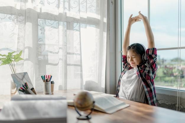 Azjatki z radością uczą się online w domu. używanie laptopów i słuchawek jako narzędzi pomagających w nauce online.