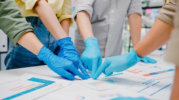 Azjatyccy biznesmeni dyskutujący na temat burzy mózgów na spotkaniach biznesowych wymieniają się danymi, nosząc maskę i rękawiczki do pracy w nowym normalnym biurze. styl życia i dystans społeczny po koronawirusie.