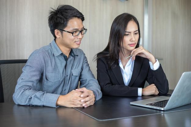 Azjatyccy biznesmeni i grupa korzystająca z notebooka dla partnerów biznesowych omawiających dokumenty i pomysły na spotkaniu oraz kobiety biznesu uśmiechnięte zadowolone z pracy