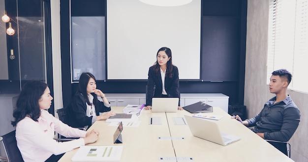 Azjatyccy biznesmeni i grupa używa notatnika dla spotykać poważny o pracy