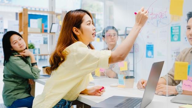 Azjatyccy biznesmeni omawiający biznesową burzę mózgów spotykają się razem, dzielą się danymi i piszą na akrylowej ściance stojącej w nowym normalnym biurze. styl życia dystans społeczny i praca po koronawirusie.