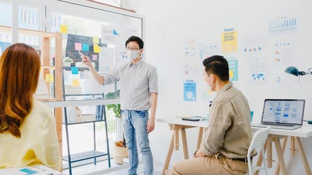 Azjatyccy biznesmeni spotykają się podczas burzy mózgów, przeprowadzają pomysły na prezentacje biznesowe, projektują kolegów i noszą ochronną maskę na twarz w nowym normalnym biurze. styl życia i praca po koronawirusie.