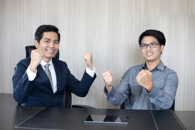 Azjatyccy biznesmeni sukces i zwycięska koncepcja - szczęśliwy zespół z podniesionymi rękami świętujący przełom i osiągnięcia