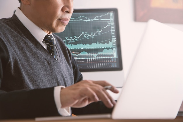 Azjatyccy biznesmeni w nowoczesnym biurze, korzystający z nowoczesnego laptopa, przeglądający rynek giełdowy i wyniki biznesowe oraz analizę ryzyka inwestycyjnego lub zwrotu z inwestycji, roi.