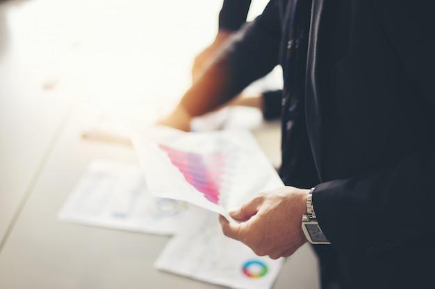 Azjatyccy bizneswomany trzyma dokumenty dla analizy na biuro stole z laptopem