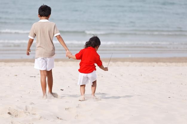 Azjatyccy bracia trzymający się za ręce na tropikalnej plaży