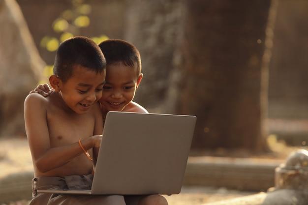 Azjatyccy chłopcy świetnie się bawią, szukając informacji w internecie. koncepcja dzieci wiejskich z dostępem do zasobów internetowych