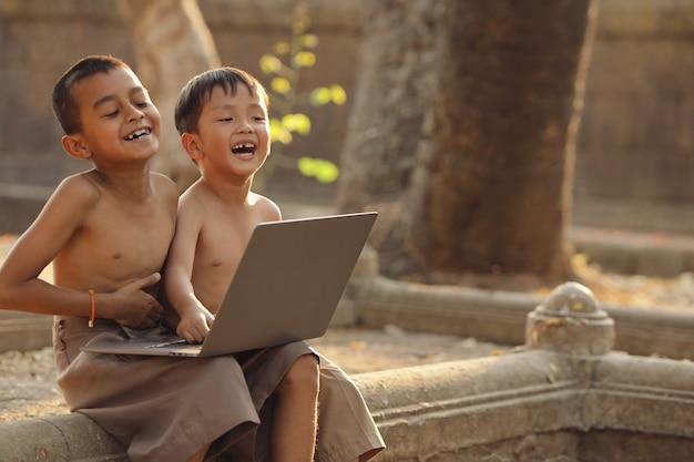 Azjatyccy chłopcy świetnie się bawią, szukając informacji w internecie.