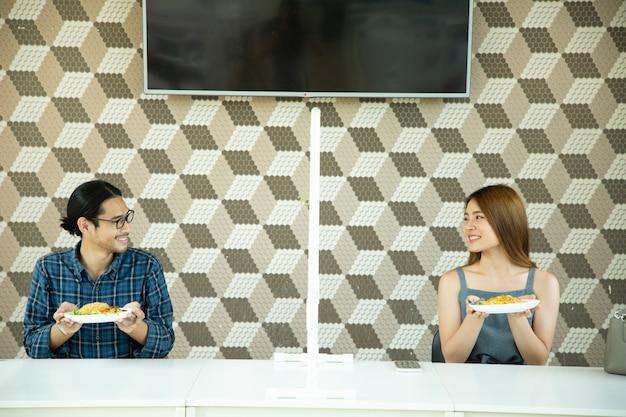 Azjatyccy dystans społeczny dla bezpieczeństwa przed wirusem koronowym w restauracji.nowa norma dla izolacji bezpieczeństwa społecznego.tajski zwyczaj trzymania jedzenia na pokaz nowego izolowanego.