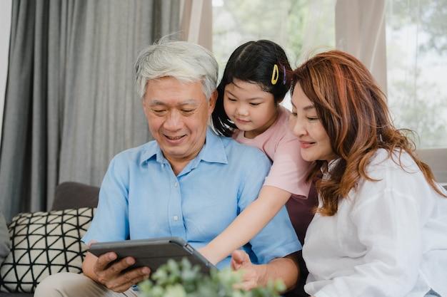 Azjatyccy dziadkowie i wnuczka używa pastylkę w domu. starszy chińczyk, dziadunio i babcia szczęśliwi, wydajemy rodzinnemu czasowi relaksować z młodą dziewczyną sprawdza ogólnospołecznych środki, kłama na kanapie w żywym izbowym pojęciu