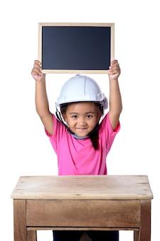Azjatyccy dzieci jest ubranym zbawczego hełm i ono uśmiecha się z chalkboard odizolowywającym na białym tle. koncepcja dzieci i edukacji