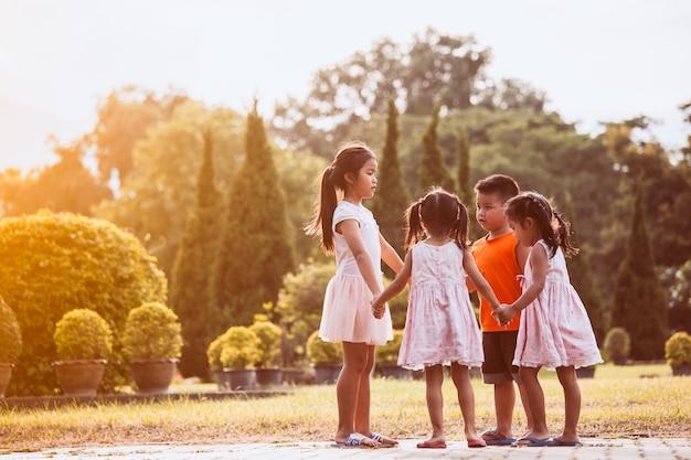 Azjatyccy dzieci trzyma rękę i robi okręgowi bawić się wpólnie w parku w rocznika koloru brzmieniu