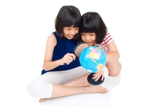 Azjatyccy dzieciaki patrzeje kulę ziemską
