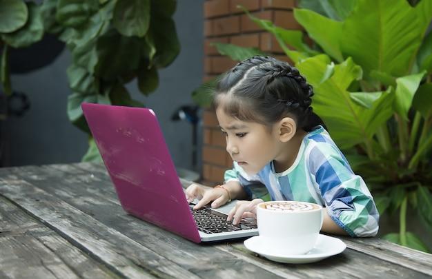 Azjatyccy dzieciaki używa laptop i filiżankę na drewno stole