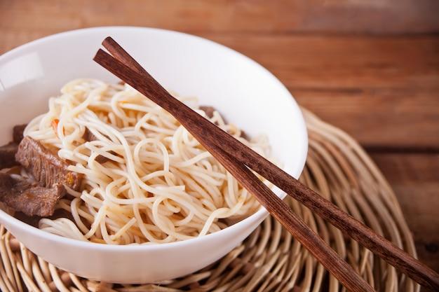 Azjatyccy kluski z wołowiną, warzywa w pucharze z pałeczkami, nieociosany drewniany tło. kolacja w stylu azjatyckim. chiński makaron japoński