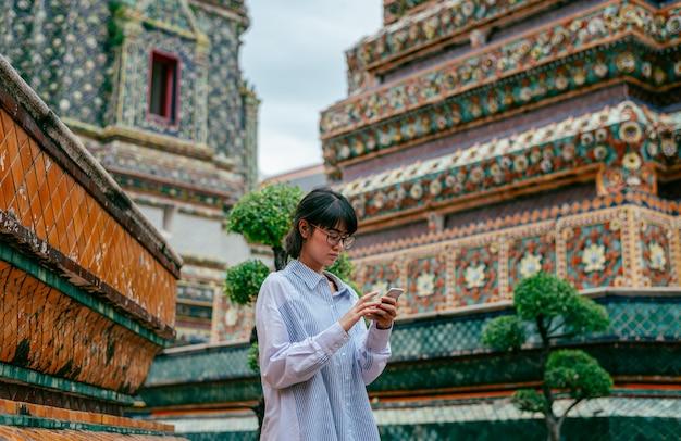 Azjatyccy kobieta podróżnicy używają smartphone dla sprawdzają jej fotografię blisko antycznego pagodowego budynku tła