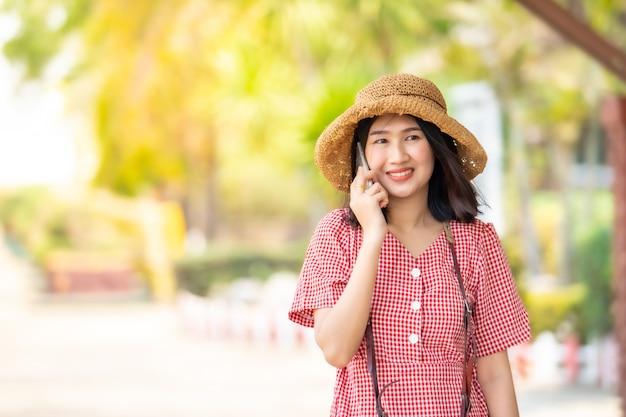 Azjatyccy kobieta turyści używają mądrze telefon przy dworcem.