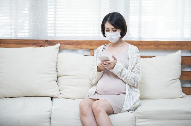Azjatyccy kobieta w ciąży jest ubranym medyczną maskę z powodu choroby, zawroty głowy używa mądrze telefon komórkowego z zmartwieniem, pandemiczny coronavirus (covid-19) pojęcie opieki zdrowotnej.