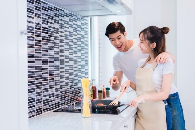 Azjatyccy kochankowie lub pary gotuje obiad w kuchennym pokoju.