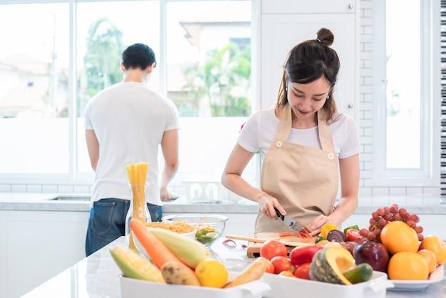 Azjatyccy kochankowie lub pary kucharstwo i pokrajać warzywa w kuchennym pokoju