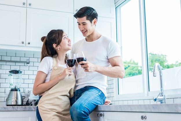 Azjatyccy kochankowie lub pary pije wino w kuchennym pokoju w domu
