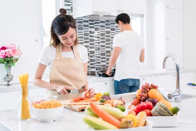 Azjatyccy kochankowie w kuchni, kobiety plasterek warzywa i kucharstwo