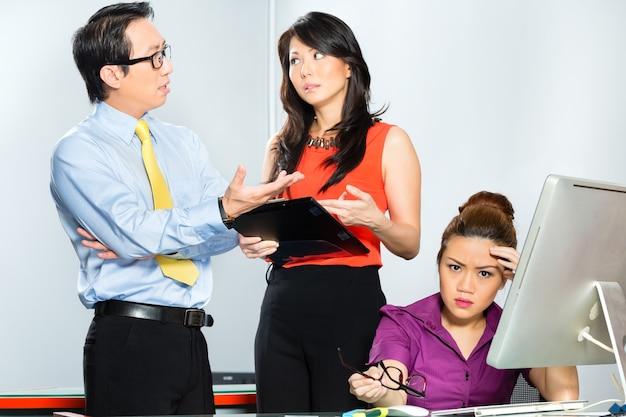 Azjatyccy koledzy lub współpracownicy i menedżer rozmawiają o zastraszaniu, stresie szykanowym lub złości pracownika z wypaleniem lub problemami