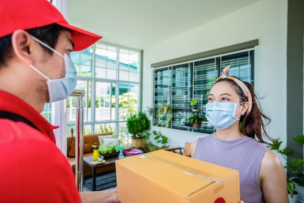 Azjatyccy kurierzy ubrani w czerwony mundur z czerwoną czapką i maską na twarz obsługujący kartony