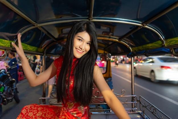 Azjatyccy ładni żeńscy turyści stawiają na czerwonej cheongsam sukni na tuk tuk samochodzie.