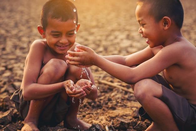 Azjatyccy lokalni chłopcy trzymający wodę ręką na suchym, popękanym gruncie zmiana klimatu ochrona środowiska i powstrzymanie koncepcji globalnego ocieplenia