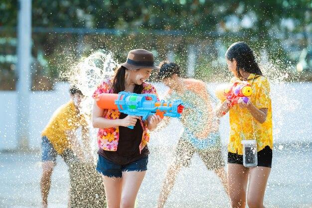 Azjatyccy ludzie bawić się z wodnymi pistoletami na słonecznym dniu