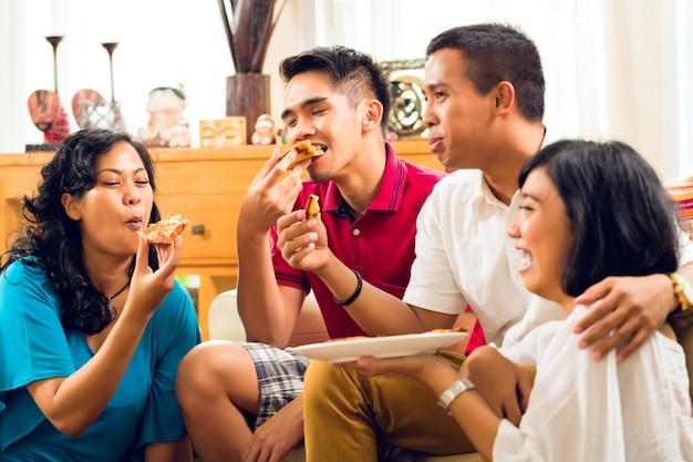 Azjatyccy ludzie je pizzę przy przyjęciem