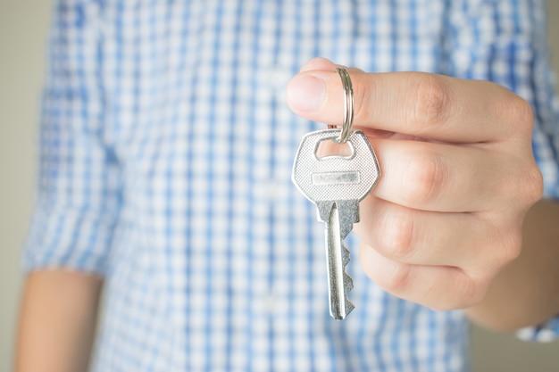 Azjatyccy ludzie trzymają klucze w błękitnych szkockich krat koszula, zamykają up.