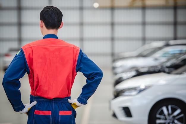 Azjatyccy mechanicy noszą kombinezony wyścigowe, aby zawrócić w warsztatach i centrach napraw samochodów.