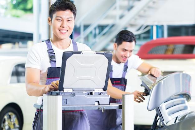 Azjatyccy mechanicy samochodowi sprawdzają silnik samochodowy za pomocą narzędzia diagnostycznego w swoim warsztacie